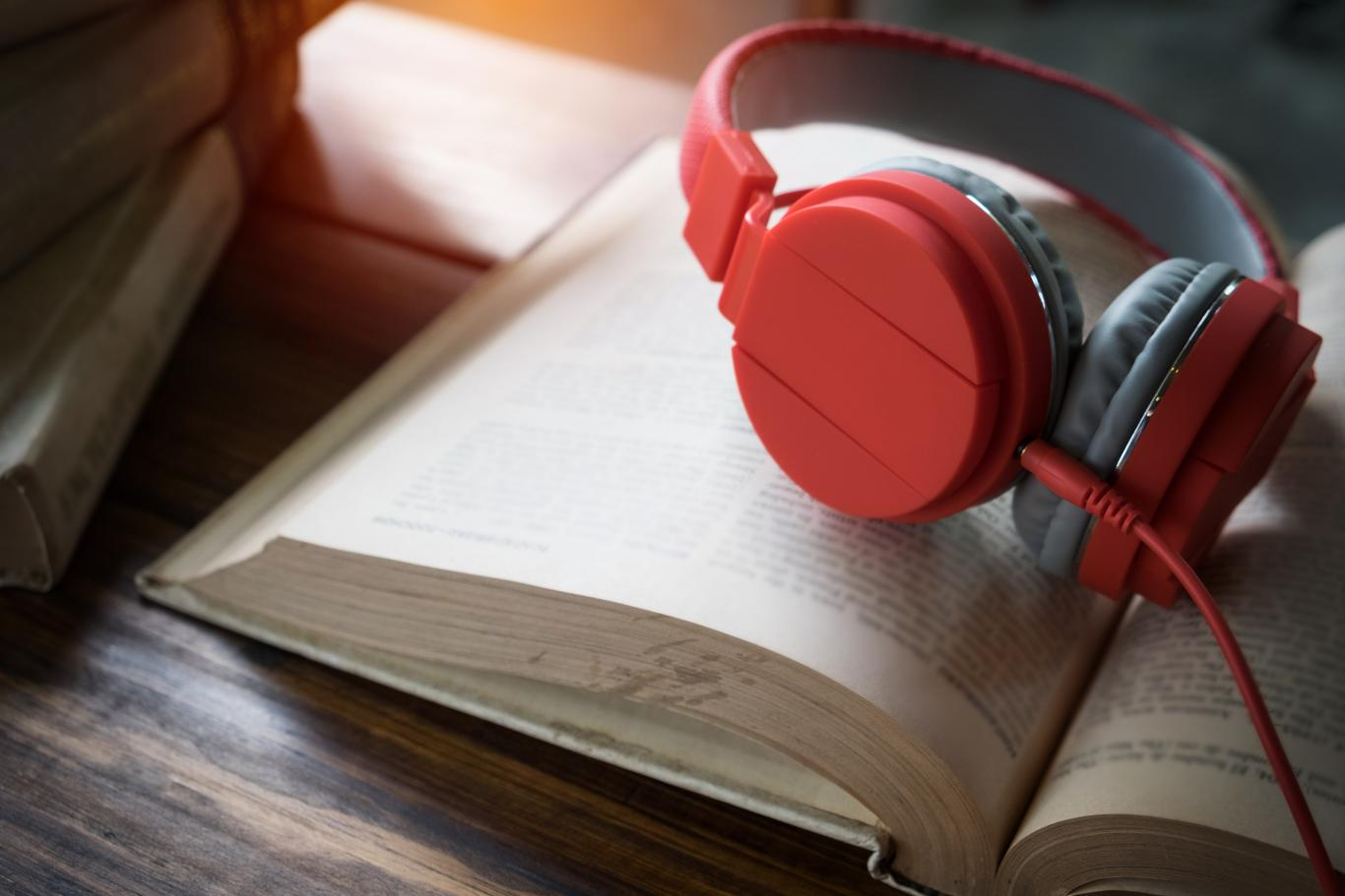 Concept-of-audiobook-Books-on-the-table-with-headphones-put-on-them