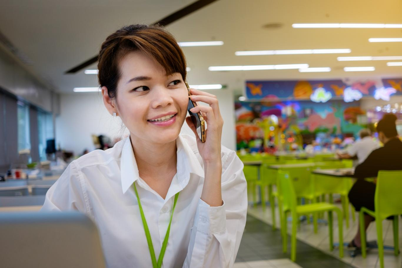 Smiling-Asian-Woman-Calling-on-Phone-and-Working-on-Laptop-at-office